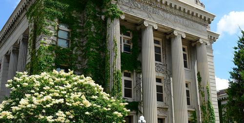 Morrill hall in summer with trees and flowers in bloom